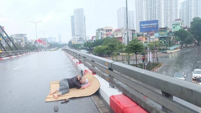 Trưa mùng 1 Tết, người đàn ông trải chiếu ra giữa phố Hà Nội để... nằm - Ảnh 2.