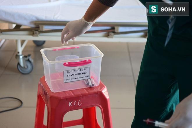 Cận cảnh một bệnh nhân trở về từ Vũ Hán nghi nhiễm virus Corona được kiểm tra y tế tại Hà Nội - Ảnh 7.