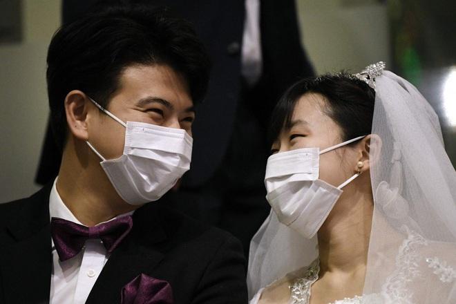 6000 cặp đôi trong đám cưới tập thể ở Hàn Quốc giữa dịch virus corona: Người đeo khẩu trang kín mít, người vẫn bất chấp trao nụ hôn - Ảnh 1.