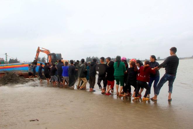 Cả làng hò nhau ra kéo tàu cá bị chìm dưới biển - Ảnh 2.