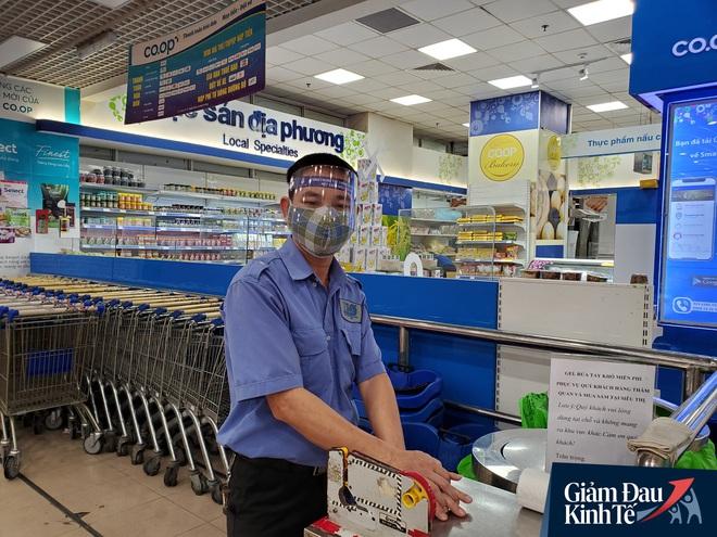 Nhân viên đeo mặt nạ bán hàng, siêu thị hàng hóa ngập kệ trong ngày đầu cách ly xã hội - Ảnh 3.