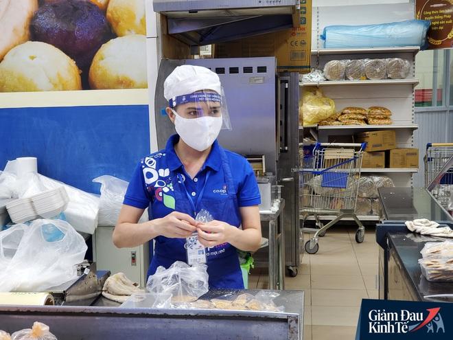 Nhân viên đeo mặt nạ bán hàng, siêu thị hàng hóa ngập kệ trong ngày đầu cách ly xã hội - Ảnh 2.