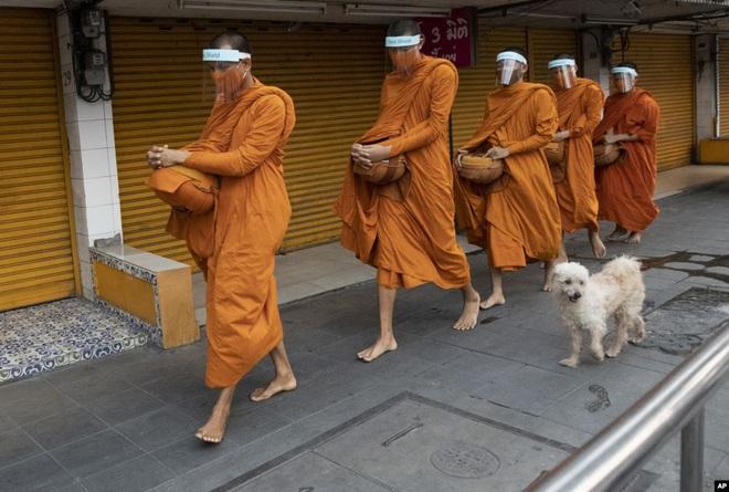 24h qua ảnh: Các nhà sư che kín mặt đi khất thực ở Thái Lan - Ảnh 3.