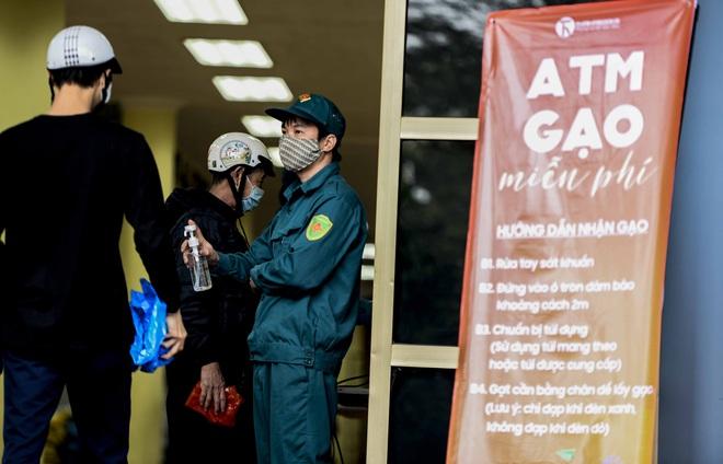 [Ảnh] Nhiều người đội mưa đến nhận gạo tại cây ATM gạo miễn phí ở Hà Nội - Ảnh 3.