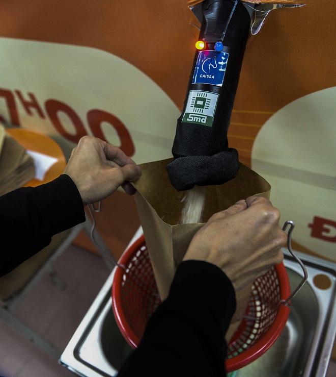 [Ảnh] Nhiều người đội mưa đến nhận gạo tại cây ATM gạo miễn phí ở Hà Nội - Ảnh 10.
