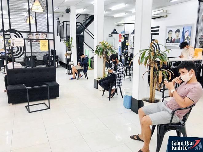 Mở cửa sau khi nới cách ly, cửa hàng cắt tóc hạn chế nhận khách do quá tải - Ảnh 4.
