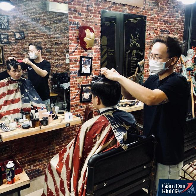 Mở cửa sau khi nới cách ly, cửa hàng cắt tóc hạn chế nhận khách do quá tải - Ảnh 1.