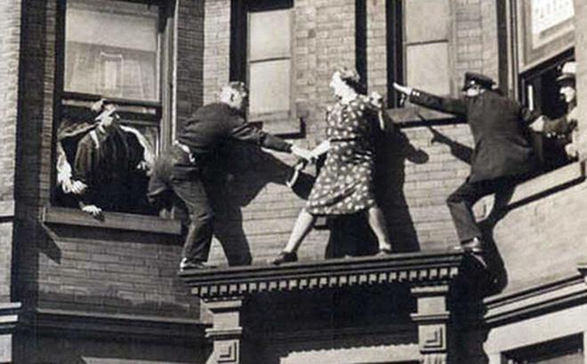 Người phụ nữ vung tay chống trả cảnh sát trên gờ tường và câu chuyện phía sau bức ảnh khiến nhiều người xót xa