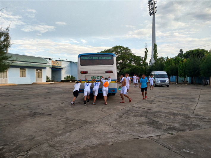 4 cầu thủ đội An Giang đẩy xe buýt chết máy - Ảnh 1.