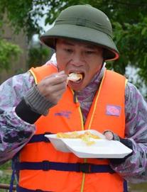 Miếng cơm ăn vội dưới mưa trên đường đưa đồ tiếp tế cho dân bị lũ cô lập ở Quảng Bình