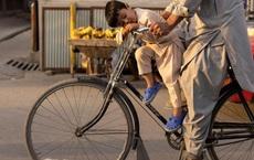 24h qua ảnh: Cậu bé ngồi ngủ ngon lành trên xe đạp của bố