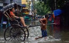 24h qua ảnh:  Phu xe chở khách trên đường phố ngập nước