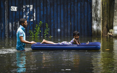 24h qua ảnh:  Bố đẩy nệm hơi chở con gái trên phố ngập lụt