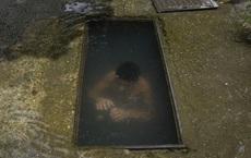 7 ngày qua ảnh: Cậu bé tắm mát dưới cống thoát nước