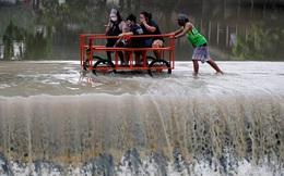 24h qua ảnh: Người đàn ông đẩy xe chở khách qua dòng nước lũ ở Philippines