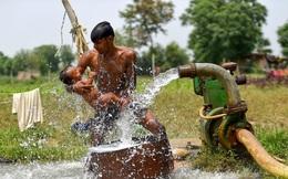 24h qua ảnh: Bố tắm mát cho con nhỏ dưới vòi máy bơm nước