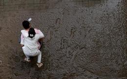 24h qua ảnh: Người đàn ông cõng vợ trên đường phố đầy bùn đất
