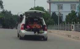 Chiếc ô tô bật mở cốp, những cánh tay vẫy chào khiến cả phố thất kinh tự hỏi: Tài xế là ai?