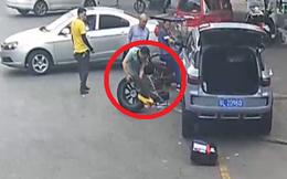 Bánh xe bị khóa vì đỗ sai quy định, người đàn ông tháo ngay giữa đường, thay bằng bánh dự phòng để tránh bị phạt