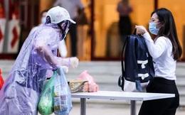 Người dân mặc áo mưa tiếp tế lương thực vào trung tâm thương mại bị phong toả