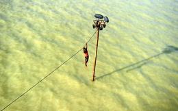 TG 24h qua ảnh: Nam thanh niên 'vắt vẻo' đu dây điện tránh nước lũ