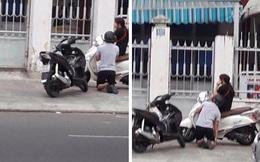 Cô gái ngồi trên xe, chàng trai quỳ sụp xuống xin lỗi