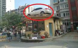 """Tài xế cùng xe hơi chễm chệ """"ngự"""" trên nóc nhà vì đỗ sai quy định"""