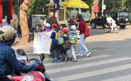 Các bé mẫu giáo cầm tờ giấy đi sang đường, dòng chữ bên trên khiến người lớn chột dạ