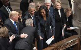 Ông George W.Bush tái hiện màn trao kẹo cho bà Obama trong tang lễ cha
