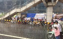 Hà Nội mưa dông lớn, hình ảnh trú mưa của người đi đường lại thành chủ đề gây tranh cãi