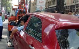 """Tài xế """"cố thủ"""", hút thuốc trong ô tô dù xe bị kéo đi vì đậu sai quy định"""