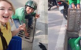 Hình ảnh đẹp: Hai tài xế GrabBike chui xuống cống để nhặt đồ hộ nữ du khách nước ngoài