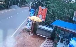 Ngồi trên xe máy còn cầm ô, người phụ nữ bị gió thổi bay xuống đường