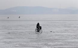 24h qua ảnh: Người Triều Tiên đạp xe trên mặt sông đóng băng