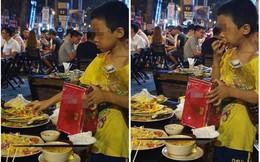 Bốc vội miếng thịt thừa nhét vào miệng, cậu bé lang thang khiến mọi người ngoái lại nhìn