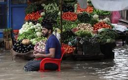 24h qua ảnh: Người đàn ông ngồi bán rau trên dòng nước đục ngầu do lụt lội