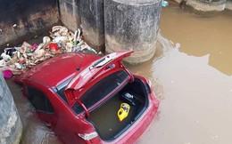 Ô tô màu đỏ nằm dưới mương, rác thải vây xung quanh khiến nhiều người tò mò