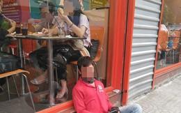 Bức ảnh thanh niên ngủ ngồi, tựa vào bậc cửa quán ăn khiến dân mạng chia phe tranh cãi