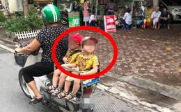 Hai đứa bé ngồi sau yên xe máy trên đường, một chi tiết khiến dân mạng chú ý