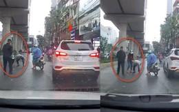 Clip cô gái làm rớt xấp tiền ra đường Hà Nội, 2 cụ ông tham lam lao tới nhặt rồi bỏ đi