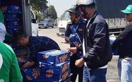 Hàng trăm thùng bia trên xe tải rơi xuống đường, người dân kéo nhau gom bia giúp tài xế