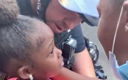 Cảm động hình ảnh chú cảnh sát ôm lấy bé gái da màu đang òa khóc giữa biểu tình sau khi nhận được câu hỏi gây ám ảnh