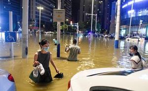 """Nước ngập đến đầu gối, người Vũ Hán đi chân trần đi làm; đường núi sụt lún, xe cần cẩu thành """"đò qua sông"""""""