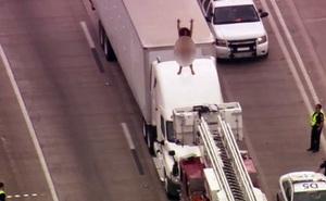 Kẹt cao tốc 2 tiếng vì... phụ nữ cởi đồ leo nóc xe