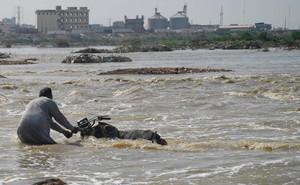 """24h qua ảnh: Người đàn ông Pakistan cố """"cứu"""" chiếc mô-tô khỏi dòng lũ"""
