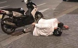 Hai người đàn ông mặc áo sơ mi trắng, vứt xe giữa đường rồi cùng nhau lên vỉa hè... ngủ
