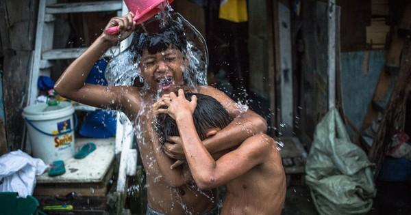 24h qua ảnh: Trẻ em tắm ngoài trời tại khu ổ chuột ở Philippines