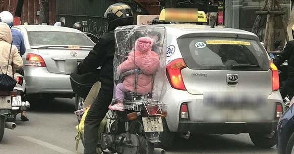 Giữa một sớm mai rét mướt, bức ảnh bé con ngồi sau xe bố trùm kín nilon khiến lòng ta ấm áp