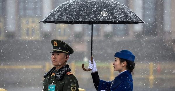 7 ngày qua ảnh: Nữ lễ tân cầm ô che tuyết cho lính gác Trung Quốc
