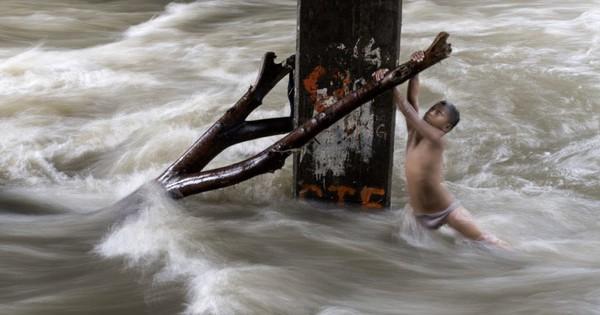24h qua ảnh: Cậu bé mạo hiểm chơi dưới dòng nước chảy xiết ở Philippines